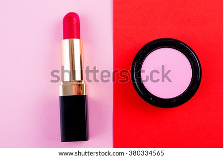 Lipstick, eye shadow and brush in bright fashion background. Pink, red and fuchsia makeup - stock photo