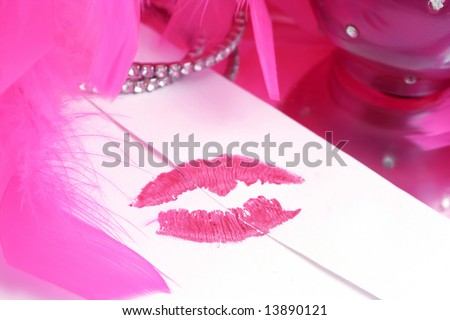 lipstick kiss on letter envelope surrounded byglamorous  pink feather boa  ( sealed with a kiss ) - stock photo