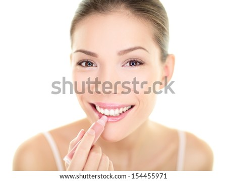 Lipstick makeup woman putting lip balm care. Beauty Asian girl applying color moisturizer on lips getting ready and looking at herself in the mirror smiling happy. Multi-ethnic Asian Caucasian model. - stock photo