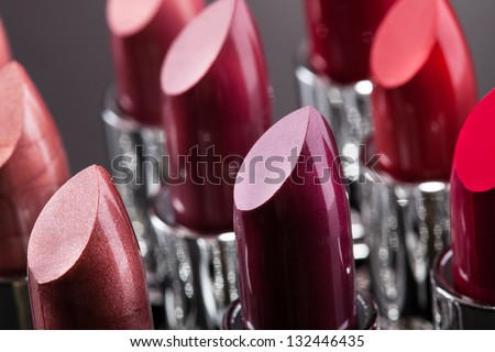 Lipsticks In A Row Isolated Over Gray Background - stock photo