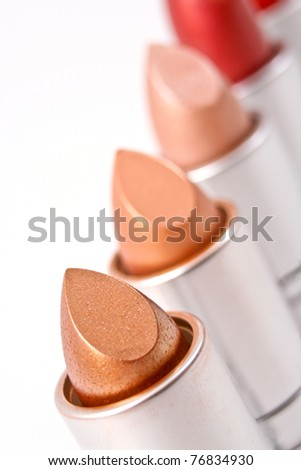 Lipsticks in straight line isolated on white background - stock photo