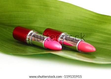 lipsticks on green leaf isolated on white - stock photo