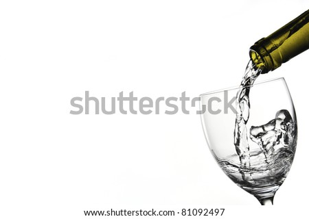 Liquid being poured into wine glass from bottle in a white background