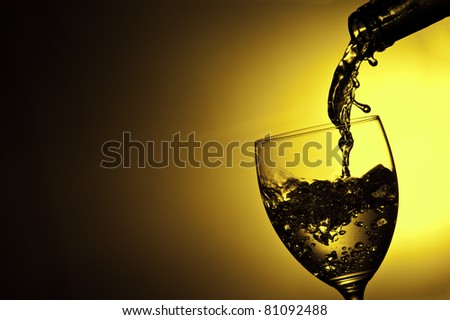 Liquid being poured into wine glass from bottle in a yellow background - stock photo
