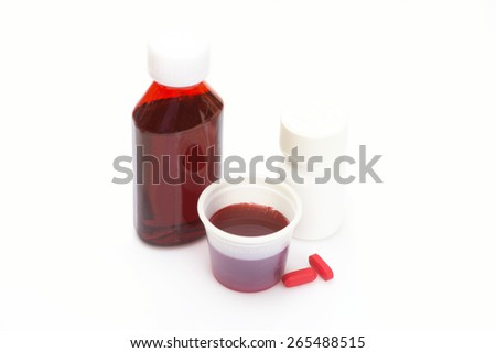 Liquid cold medicine in cup with bottle of medication and red pills. - stock photo