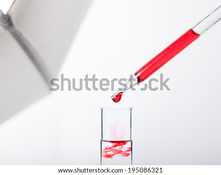liquid dripping from pipette into test tube isolated - stock photo