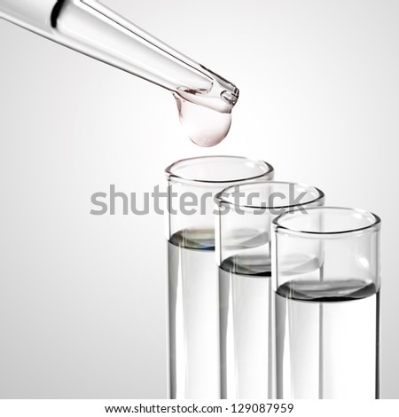 Liquid drop from laboratory glass pipette to test tube - stock photo