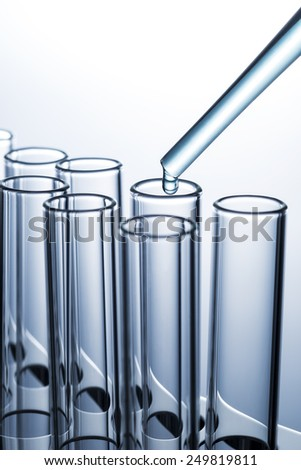 Liquid drop from pipette to laboratory glass test tube - stock photo