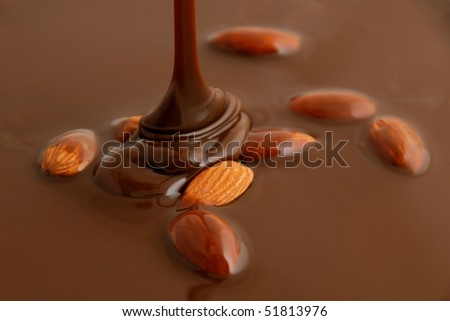 Liquid hot milk chocolate falling on almonds - stock photo