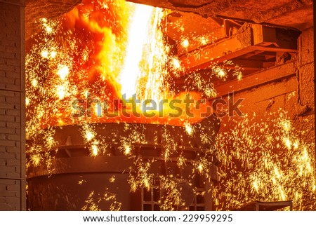 Liquid iron from ladle in the steelworks - stock photo