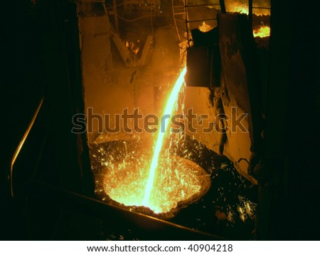 Liquid metal from casting ladle. Ferrous metallurgy. - stock photo