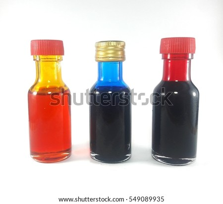 Liquid orange red, red and blue food color additive over white background