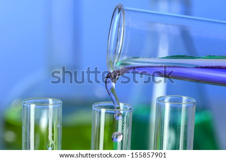 Liquid pouring into test tube from graduated cylinder in laboratory - stock photo