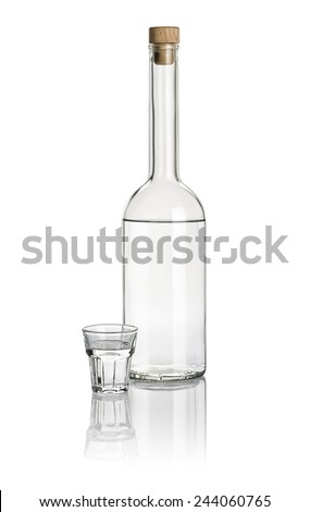 Liquor bottle and beveled shot glass filled with clear liquid - stock photo