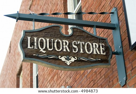 Liquor store sign hanging on a red brick wall. - stock photo