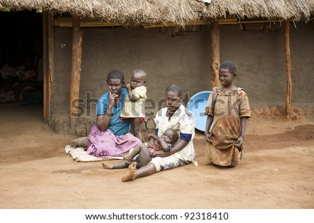 LIRA, UGANDA - JUNE 9: An unidentified family sits on the dirt ground outside their thatched roof hut in Lira, Uganda on June 9, 2007. UNHCR estimates there to be over 136,000 refugees in Uganda. - stock photo