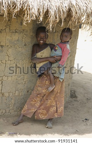 LIRA, UGANDA - JUNE 9: An unidentified girl holds her baby brother under thatched roof of their hut in Lira, Uganda on June 9, 2007. UNHCR estimates there to be over 136,000 refugees in Uganda. - stock photo
