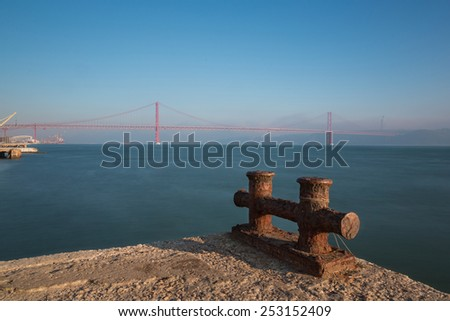 "Lisboa, Portugal, Europe - Pier view to ""25 April Bridge"" a Lisbon landmark,  late afternoon in a foggy and windy day. - stock photo"