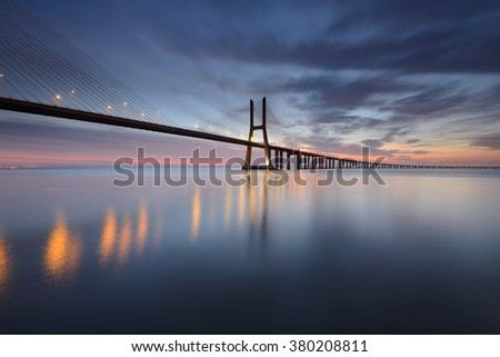 Lisbon and Vasco da Gama Bridge are an amazing tourist destination because their urban landscapes and its monuments. The Bridge crosses the Tagus River, and is one of the longest bridges in the world. - stock photo