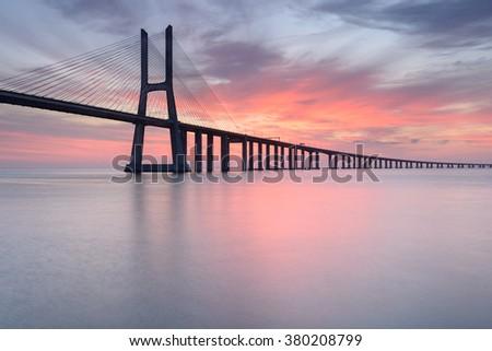 Lisbon at Sunrise, red color light landscape. Vasco da Gama Bridge are an amazing tourist destination. The Bridge crosses the Tagus River, and is one of the longest bridges in the world. - stock photo