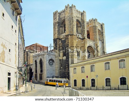 Lisbon Cathedral (Santa Maria Maior) and traditional yellow tram on the street, Portugal - stock photo