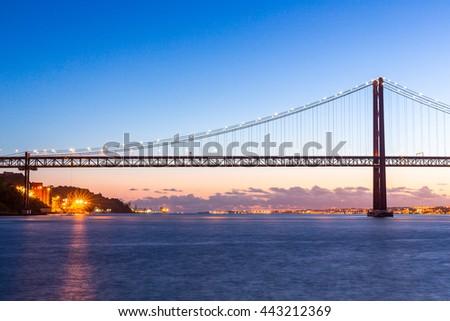 Lisbon cityscape with 25 de Abril suspension Bridge, Portugal at dusk - stock photo