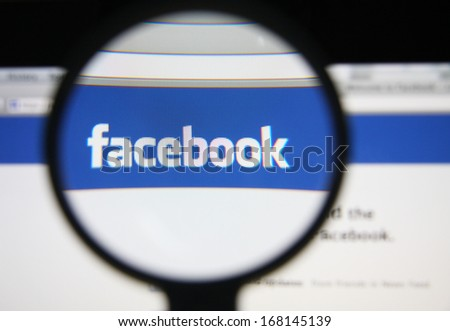 LISBON - DECEMBER 20, 2013: Photo of Facebook homepage on a monitor screen through a magnifying glass. - stock photo