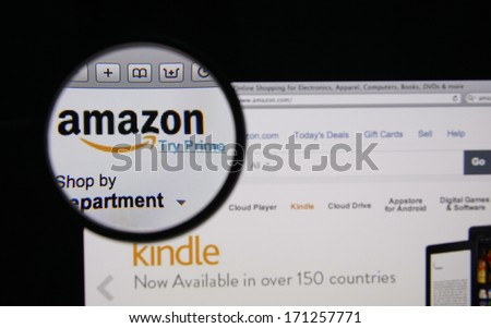 LISBON - JANUARY 14, 2014: Photo of Amazon homepage on a monitor screen through a magnifying glass.