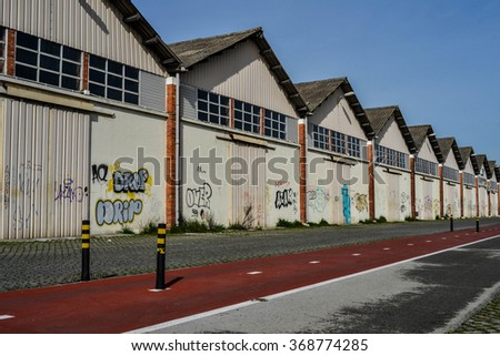 LISBON - JANUARY 27: Warehouses on waterfront with bike path in front in Lisbon, Portugal on January 27, 2016