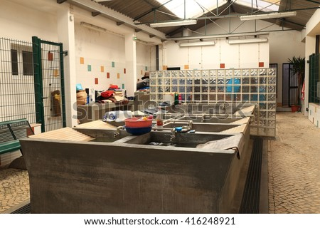 Lisbon, Portugal, April 25 2016, Communal laundry facility in the crowded Alfama district lie empty on a public holiday, on April 15 2016 in Lisbon, Portugal. - stock photo
