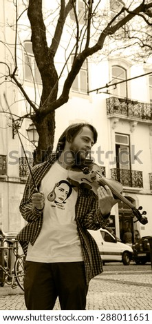 "LISBON, PORTUGAL - APRIL 22, 2015: Unidentified violinist wearing t-shirt with portrait of Amalia Rodrigues  ( known as ""Queen of Fado"") plays music at city square for the tourists and citizens. - stock photo"