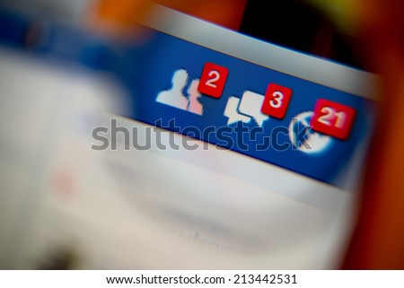 LISBON, PORTUGAL - AUGUST 27, 2014: Photo of Facebook alerts of friend requests, messages inbox and notifications on a monitor screen through a magnifying glass. - stock photo