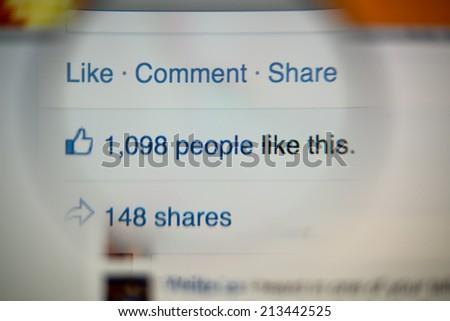 LISBON, PORTUGAL - AUGUST 27, 2014: Photo of Facebook notifications of Likes and Shares on a monitor screen through a magnifying glass. - stock photo
