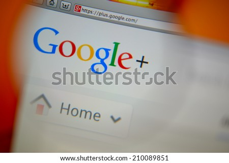 LISBON, PORTUGAL - AUGUST 3, 2014: Photo of Google+ homepage on a monitor screen through a magnifying glass. - stock photo