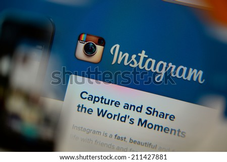 LISBON, PORTUGAL - AUGUST 3, 2014: Photo of Instagram homepage on a monitor screen through a magnifying glass. - stock photo