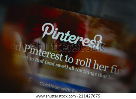 LISBON, PORTUGAL - AUGUST 3, 2014: Photo of Pinterest homepage on a monitor screen through a magnifying glass. - stock photo