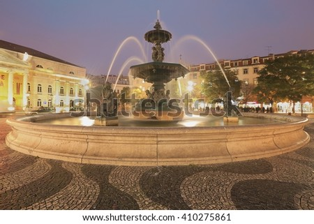LISBON, PORTUGAL - DECEMBER 24 2015: Monumental fountain in Rossio Square at twilight in Lisbon. It is a popular meeting point for tourists and locals