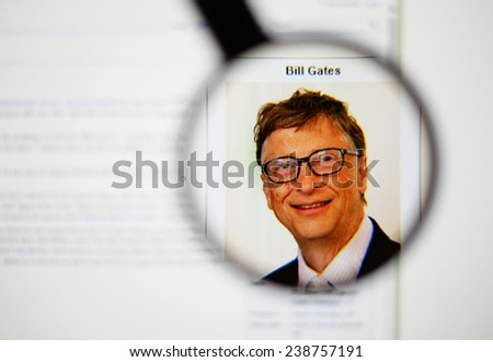 LISBON, PORTUGAL - DECEMBER 16, 2014: Photo of Wikipedia article page about Bill Gates on a monitor screen through a magnifying glass.    - stock photo