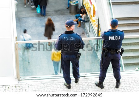 LISBON, PORTUGAL - DECEMBER 5, 2013: Two national police watching from a balcony the main entrance to the Oriente Railway Station in Lisbon. - stock photo