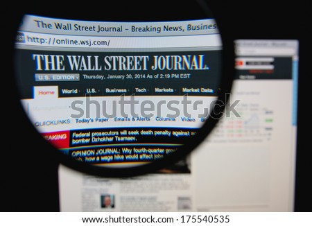 LISBON, PORTUGAL - FEBRUARY 8, 2014: Photo of The Wall Street Journal homepage on a monitor screen through a magnifying glass. - stock photo