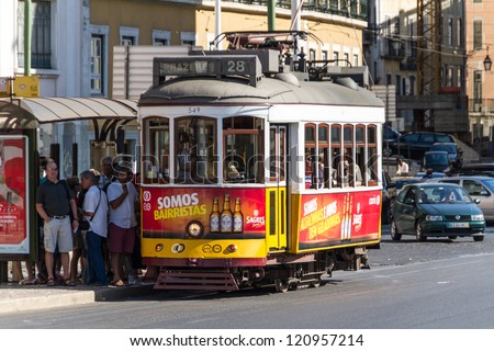 LISBON, PORTUGAL - JUN 25: Traditional yellow and red trams downtown Lisbon on Jun 25, 2012. Trams are used by everyone and also keep the traditional style of the historic center of Lisbon.