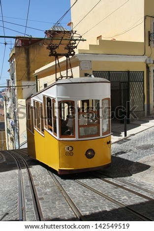 LISBON, PORTUGAL - JUNE 3: A traditional tram is making its way through a narrow street in Lisbon, Portugal on June 3, 2013. The five urban tramway lines mainly serve as a tourist attraction.
