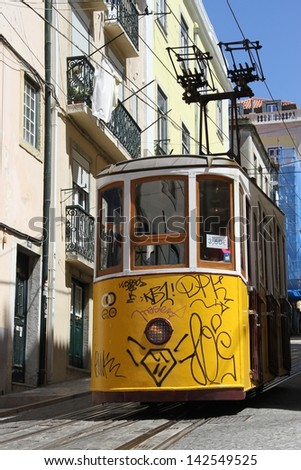 LISBON, PORTUGAL - JUNE 3: A traditional tram is making its way through a narrow street in Lisbon, Portugal on June 3, 2013. The five urban tramway lines mainly serve as a tourist attraction. - stock photo