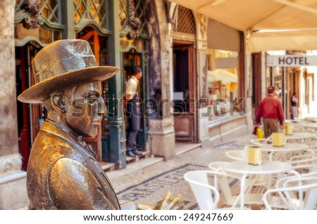 LISBON, PORTUGAL - MARCH 18: Statue of Fernando Pessoa outside of Cafe A Brasileira on March 18, 2014 in Lisbon, Portugal. This iconic statue and the cafe itself are visited by thousands of tourists - stock photo