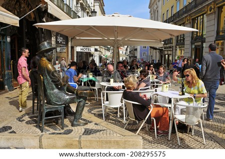 LISBON, PORTUGAL - MARCH 17: The crowded terrace of Cafe A Brasileira with the Statue of Fernando Pessoa on March 17, 2014 in Lisbon, Portugal. This statue and the cafe are visited for many tourists - stock photo