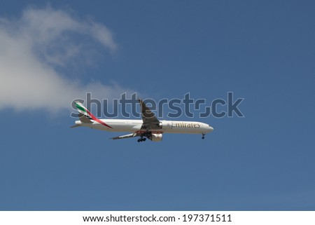 LISBON, PORTUGAL - MAY 26, 2014: An Emirates aircraft approaching the Lisbon airport. Emirates is the largest airline in the Middle East, operating nearly 3,400 flights per week. - stock photo