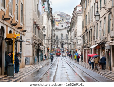 LISBON, PORTUGAL - MAY 2, 2012 - The Lisbon cityscape with red tram on Rua Vitor Cordon during the rain, on May 2 in Lisbon. People try to hide from the rain and visit shops and cafes.