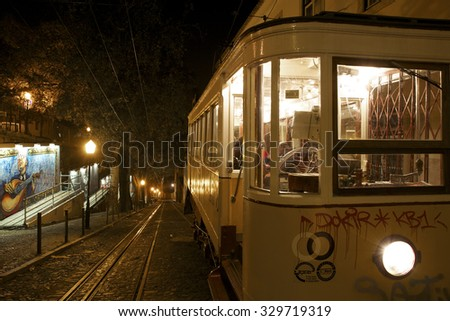 LISBON, PORTUGAL, NOVEMBER 28: Front view of the yellow vintage famous Bica tramway at night with graffiti of musician playing guitar on wall by unknown artist in Bairro Alto, Lisbon, Portugal 2011 - stock photo