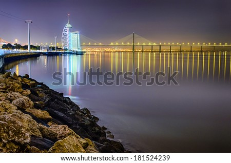 LISBON, PORTUGAL - NOVEMBER 14: The modern Park of the Nations area in Lisbon, Portugal at night on November 14, 2012 with the Vasco da Gama bridge in the background - stock photo