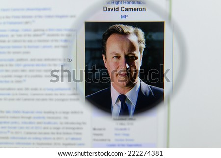 LISBON, PORTUGAL - OCTOBER 8, 2014: Photo of Wikipedia article page about David Cameron on a monitor screen through a magnifying glass. - stock photo